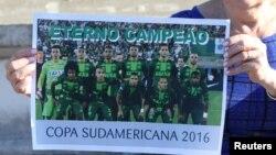 브라질프로축구팀 샤페코엔시 소속 선수들이 지난 28일 비행기 추락 사고로 사망한 가운데 축구팬이 이들의 사진이 담긴 포스터를 들고 있다.
