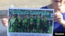 Seorang penggemar tim sepakbola Chapecoense menunjukkan poster tim tersebut di stadion Arena Conda di Chapeco, Brazil, 29 November 2016. (REUTERS/Paulo Whitaker)