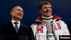FILE: Russian President Vladimir Putin, left, laughs with Russia's gold medalist bobsleigh athlete, Alexander Zubkov, during the 2014 Sochi Winter Olympics closing ceremony Feb. 23, 2014.
