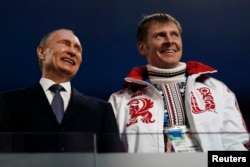 FILE: Russian President Vladimir Putin, left, laughs with Russia's gold medallist bobsleigh athlete, Alexander Zubkov, during the 2014 Sochi Winter Olympics closing ceremony Feb. 23, 2014.