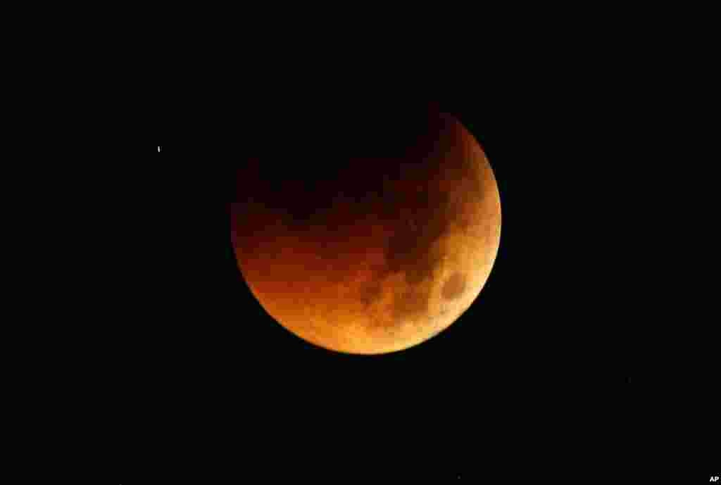 The Earth completely casts its shadow over the moon in a total lunar eclipse as seen in Manila, Philippines before dawn on Thursday. The total lunar eclipse was also visible in most parts of Asia. (AP Photo/Bullit Marquez)