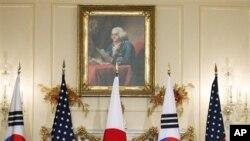 ລັດຖະມົນຕີຕ່າງປະເທດສະຫະລັດ Hillary Rodham Clinton ໂດຍມີ ລັດຖະມົນຕີຕ່າງປະເທດເກົາຫລີໃຕ້ Kim Sung-hwan (ຂວາ) ກັບລັດຖະມົນຕີຕ່າງປະເທດຍີ່ປຸ່ນ Seiji Maehara (ຊ້າຍ) ອ້ອມຂ້າງ, ກ່າວຄໍາ ຖະແຫລງ ກ່ອນໄຂກອງປະຊຸມ 3 ຝ່າຍ ທີ່ກະຊວງຕ່າງປະເທດສະຫະລັດ ທີ່ວໍຊິງຕັນ, ເມື່ອວັນທີ 6