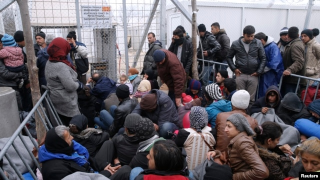 Migrants wait to cross the Greek-Macedonian border at a makeshift camp, near the village of Idomeni, Greece March 7, 2016.