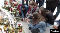 Sekelompok turis menyalakan lilin di depan museum Bardo di Tunis, Tunisia (27/3)