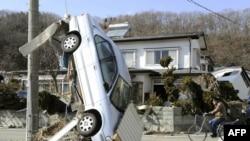 Xe cộ bị lật ngược trên đường phố ở Miyako, đông bắc Nhật Bản. Thiên tai xảy ra vào lúc Nhật Bản đang cố gắng ứng phó với tình trạng tăng trưởng kinh tế chậm chạp và mức nợ của chính phủ tăng cao