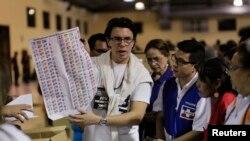 Un funcionario electoral muestra la papeleta de votación durante las elecciones municipales y legislativas de El Salvador.