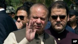 Pakistani Prime Minister Nawaz Sharif, center, with his son Hussain Nawaz, right, in Islamabad, Pakistan, June 15, 2017. Sharif appeared before a Supreme Court-appointed team investigating allegations against his family's offshore companies and money laundering.