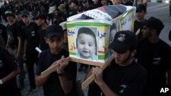 Các thanh niên Palestine khênh quan tài giả để tưởng nhớ bé trai một tuổi rưỡi mới bị các phần tử cực đoan Do Thái thiêu sống.