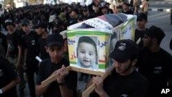"""Remaja Palestina mengenakan pakaian hitam-hitam mengusung peti mati tiruan bergambar """"Ali Dawabsheh"""", seorang bayi Palestina yang tewas akibat serangan ekstrimis Yahudi di Tepi Barat, dalam aksi unjuk rasa Sabtu (1/8)."""