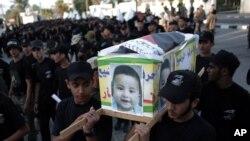 "Pemuda Palestina mengenakan pakaian hitam membawa peti mati tiruan seorang anak laki-laki berusia sati setengah tahun, Ali Dawabsheh, dengan fotonya dan tulisan Arab: ""Mereka membakar bayi ini dan saya datang untuk membalas"", ketika pemakaman simbolik dilakukan di kota Khan Younis, Jalur Gaza Selatan, Sabtu, 1 Agustus 2015. (AP Photo/ Khalil Hamra)"