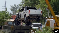 A damaged vehicle that carried military officers is removed from the site of suicide bombing on the outskirts of Fateh Jang, some 36 kilometers (22 miles) southwest of Islamabad, Pakistan, Wednesday, June 4, 2014.