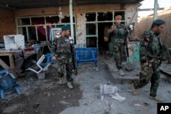 FILE - Afghan security forces inspect damages after clashes between Taliban fighters and Afghan forces in Kandahar Airfield, Afghanistan, Wednesday, Dec. 9, 2015.
