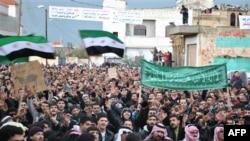 Người biểu tình vẫy cờ cách mạng và hô khẩu hiệu chống Tổng thống Syria Bashar Assad tại Homs, miền trung Syria, 27/1/2012