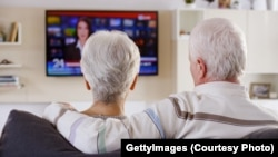 An older couple watching television in living room.