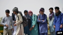 Afghan men wait in queue to cross into Iran at an Afghan-Iran border crossing in Zaranj on Sept. 8, 2021.
