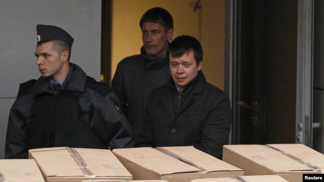 Detained opposition activist Konstantin Lebedev (R, front) is escorted out of a building of the Russian Investigative Committee in Moscow, October 17, 2012.