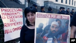 """A protester holds up a poster with writing reading in Italian """"Justice for Abu Omar"""" above a picture of Muslim cleric Osama Moustafa Hassan Nasr, also known as Abu Omar, outside Milan's court house while the trial of 26 Americans and seven Italians accused of orchestrating a CIA-led kidnapping of an Egyptian terror suspect Nasr was taking place inside the courtroom, in Milan, Italy, Sept. 23, 2009."""