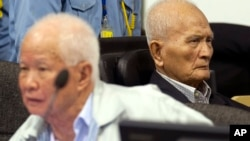 In this photo released by the Extraordinary Chambers in the Courts of Cambodia, Khieu Samphan, left, former Khmer Rouge head of state, and Nuon Chea, right, who was the Khmer Rouge's chief ideologist and No. 2 leader, sit in the court hall before they made closing statements at the U.N.-backed war crimes tribunal in Phnom Penh, file photo.