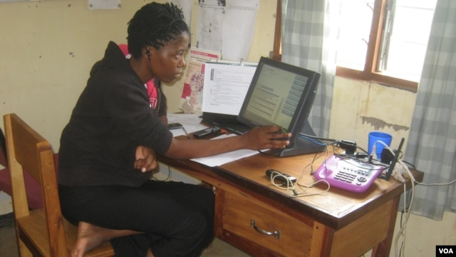 Hotline worker Hanna James assists a caller at Balaka Centre in Malawi, Jan. 13, 2014. (Lameck Masina/VOA)