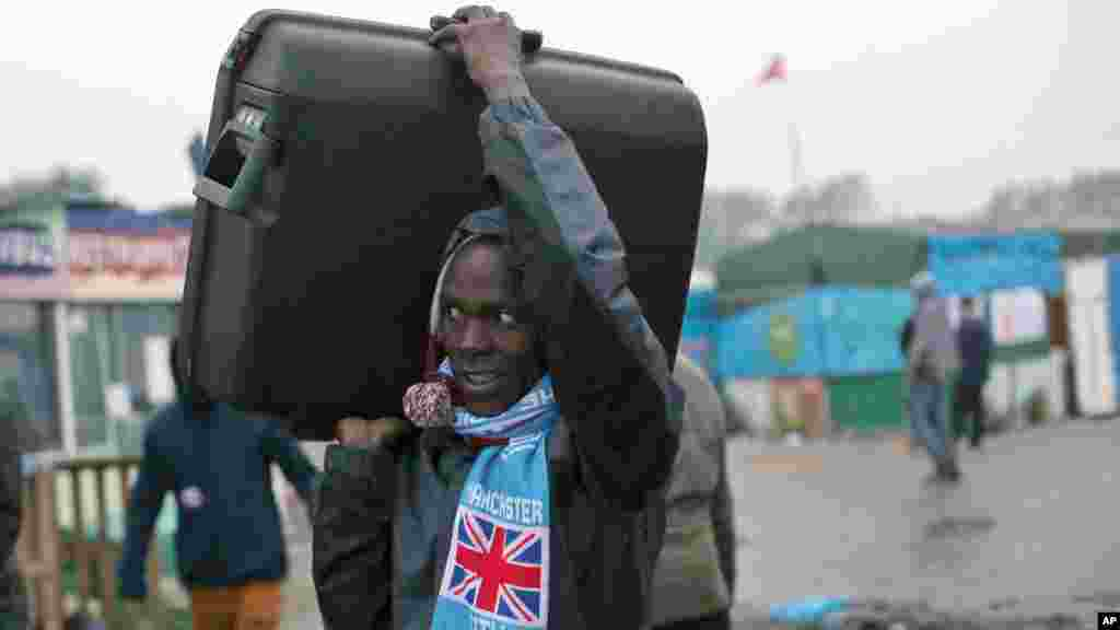 """An unidentified migrant carrying his luggage leaves a makeshift camp known as """"the jungle"""" near Calais, northern France, to register at a processing center,Oct. 24, 2016."""