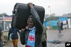 """ຊາຍອົບພະຍົບຜູ້ບໍ່ຮູ້ມາຈາກໃສ ແບກຫີບເດີນທາງ ອອກໄປຈາກສູນອົບພະຍົບຊົ່ວຄາວ ທີ່ຮູ້ຈັກກັນຄື """"the jungle"""" ຫຼື ປ່າດົງ ຢູ່ໃກ້ກັບເມືອງທ່າ Calais, ທາງພາກເໜືອຂອງ ຝຣັ່ງ ເພື່ອໄປຂຶ້ນທະບຽນ ຢູ່ທີ່ສູນຕ້ອນຮັບອົບພະຍົບ, ວັນທີ 24 ຕຸລາ 2016."""