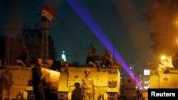 ທະຫານອີຈິບ ພາກັນຍາມ ຢູ່ຫົນທາງສາຍນຶ່ງ ໃກ້ທຳນຽບປະທານາທິບໍດີ ຂະນະທີ່ພວກສະໜັບສະໜຸນ ທ່ານ Mohamed Morsi ພວມເດີນຂະບວນເຂົ້າໄປໃກ້ໆ (19 ກໍລະກົດ 2013)