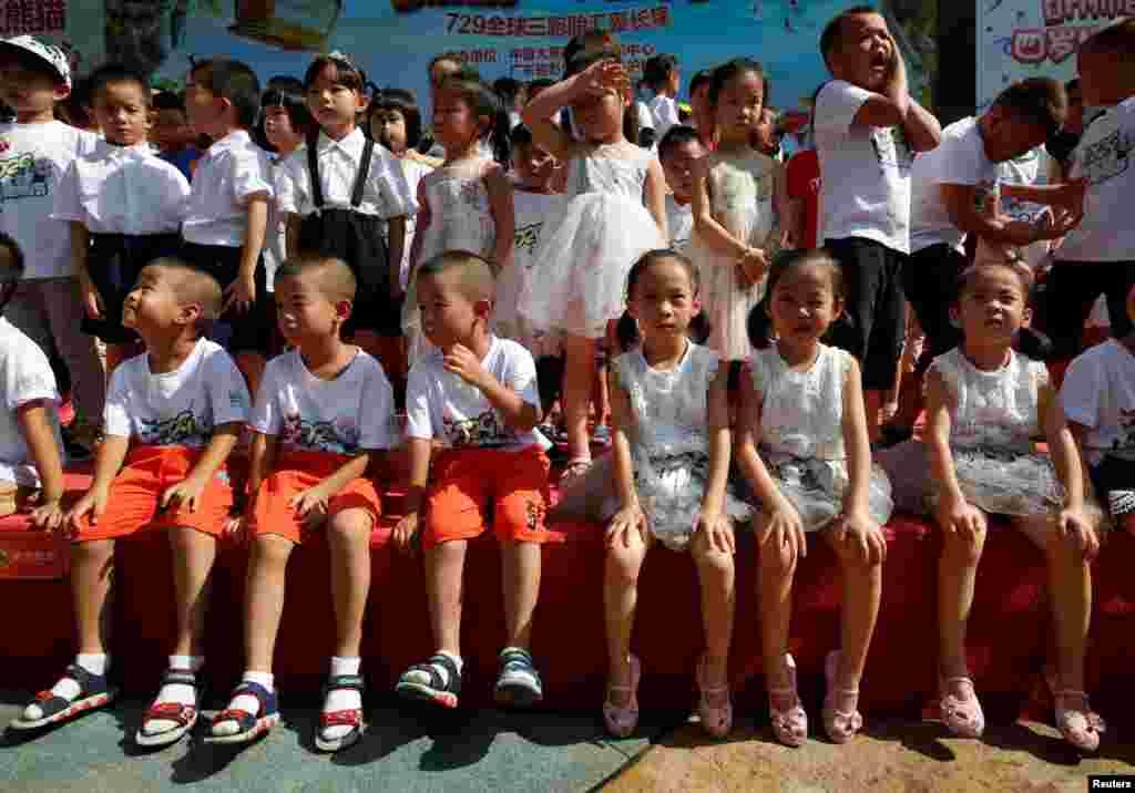 在中国广州长隆野生动物园,三胞胎儿童庆祝世界上唯一的大熊猫三胞胎萌萌、帅帅和酷酷的4岁生日(2018年7月29日)。