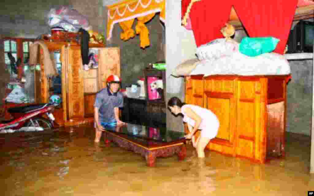 Residents move their belongings in a flooded house to higher ground in Vietnam's central province of Quang Binh, 10/18/2011