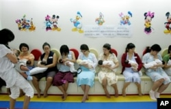Mothers in Singapore breastfeed their babies during a breastfeeding campaign.