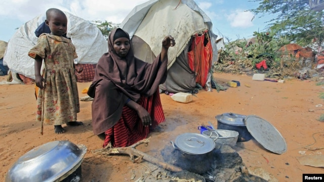 Kadija Mohamed cooks food for her children in a camp set up for internally displaced people in Dinsoor, in southern Somalia, January 5, 2012.