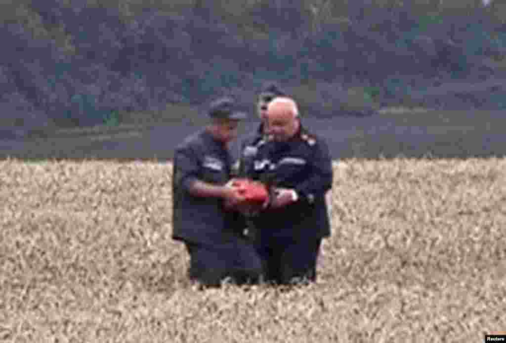 """A rescue worker shows a flight data recorder to a colleague at the crash site of Malaysia Airlines Flight MH17 in Hrabove July 18, 2014 in this still image taken from video. Rescue workers have recovered a """"black box"""" flight recorder from the wreckage of the Malaysian airliner."""