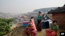 ႐ိုဟင္ဂ်ာ ဒုကၡသည္ အမ်ိဳးသမီး Anu သူသား Mohammad Anas ကို ခ်ီထားၿပီး ဘဂၤလားေဒ့ခ်္ႏိုင္ငံ Cox's Bazar အနီး Balukhali ဒုကၡသည္ စခန္းက သူတို႔တဲအျပင္ဘက္မွာ ထိုင္ေနပံု (ႏို၀င္ဘာ၊ ၁၇၊ ၂၀၁၈)