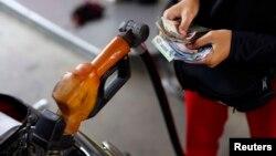 Pegawai sebuah pom bensin di Jakarta menghitung uang sambil mengisi bahan bakar bersubsidi untuk sepeda motor.