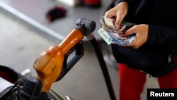 FILE - A worker at a state-owned Pertamina petrol station holds money as a motorcycle is filled with subsidized fuel in Jakarta, Oct. 31, 2014.