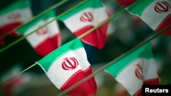 FILE - Iran's national flags are seen on a square in Tehran.