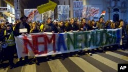 FILE - Demonstrators march through the streets of Budapest, as they protest against an internet tax planned to be introduced by the Hungarian government, for the second time in two days, in Budapest, Hungary, Oct. 28, 2014.