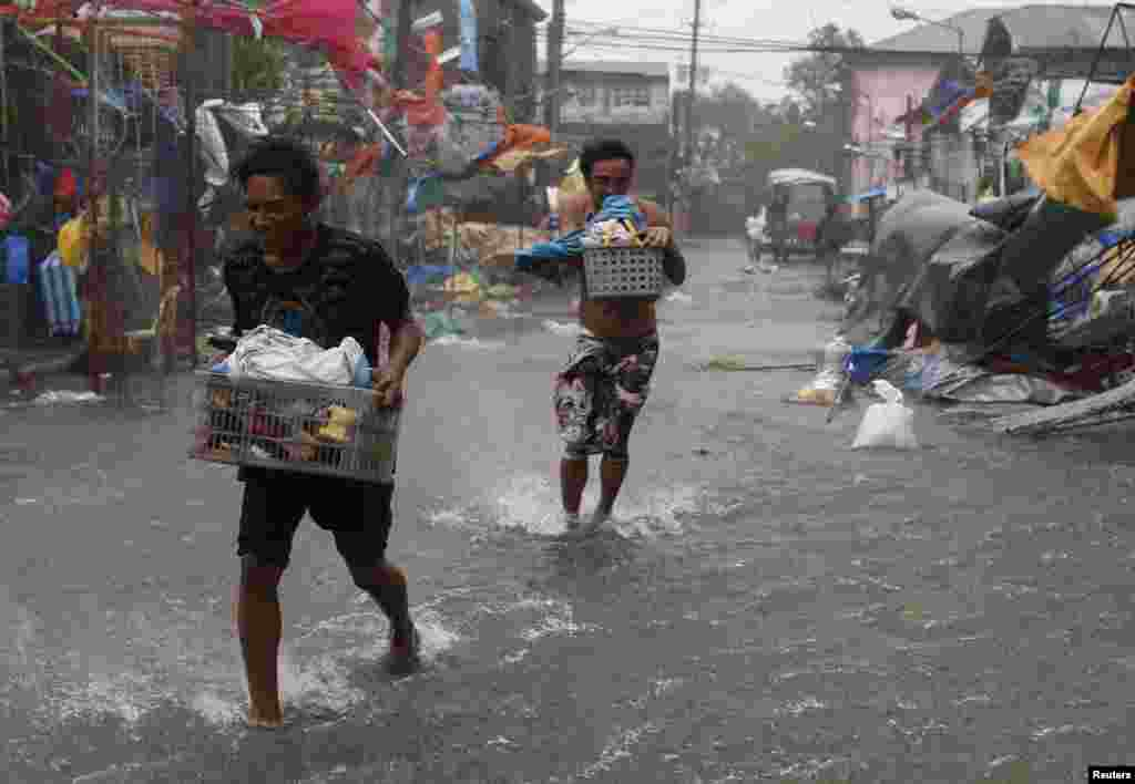 Residents carry their belongings as Typhoon Rammasun hit the town of Imus, Cavite, southwest of Manila, July 16, 2014.