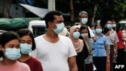 People wearing face masks amid concerns over the spread of the COVID-19 coronavirus wait in line for health check-ups in Yangon on May 17, 2020. (Photo by Sai Aung Main / AFP)