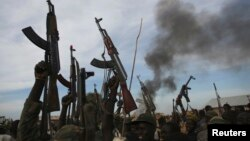 Rebel fighters hold up their rifles as they walk in front of a bushfire in rebel-controlled territory in Upper Nile State, South Sudan, Feb. 13, 2014.