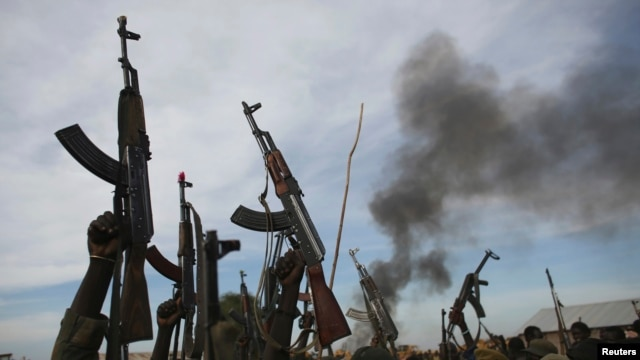 Rebel fighters hold up their rifles as they walk in front of a brushfire in a rebel-controlled territory in Upper Nile State, South Sudan, Feb. 13, 2014.