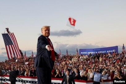 Presiden AS Donald Trump melempar masker dari panggung dalam kampanye pertamanya sejak dirawat karena terinfeksi virus corona (COVID-19) di Bandara Internasional Orlando Sanford di Sanford, Florida, Senin, 12 Oktober 2020. (Foto: Reuters)