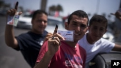 Libyan men hold their elections ID cards while celebrating election day in Tripoli, Saturday, July 7, 2012.