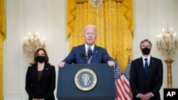 President Joe Biden speaks about the evacuation of American citizens, their families, SIV applicants and vulnerable Afghans in the East Room of the White House, Friday, Aug. 20, 2021, in Washington. Vice President Kamala Harris, left, and Secretary of State Antony Blinken, right,
