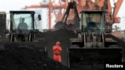 FILE - An employee walks between front-end loaders which are used to move coal imported from North Korea at Dandong port in the Chinese border city of Dandong, Liaoning province, Dec. 7, 2010.