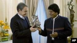 El presidente boliviano Evo Morales, derecha, regala una máscara de diablo al ex primer ministro español José Luis Rodríguez Zapatero en el palacio de gobierno en La Paz, Bolivia, el domingo 24 de junio de 2018. Morales dijo el jueves 5 de julio de 2018 que se encuentra bien y que espera ser dado de alta tras ser operado de un pequeño tumor en una clínica de La Paz.
