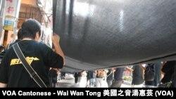 大部份遊行人士身穿黑衣、不呼口號,合力拉著大型黑布遊行