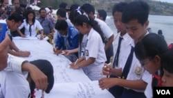 Para pelajar di Bali membubuhkan tanda tangan dalam peringatan pengeboman Bali 2005.(VOA/Muliarta)