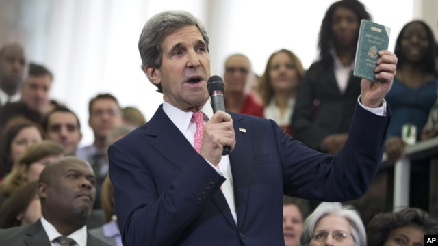 New Secretary of State John Kerry shows his first diplomatic passport he got when he was 11 years old when his father was in the foreign service, during a ceremony welcoming him as the 68th secretary of state, Feb. 4, 2013.