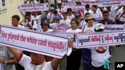 FILE - Activists hold placards as they march for a protest a government decision to allow people without full citizenship, including members of the Rohingya ethnic minority, to vote in an upcoming constitutional referendum, Feb. 11, 2015 in Yangon, Myanma