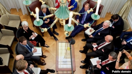 U.S. Secretary of State John Kerry - seen through a hotel chandelier - and his advisers sit with Russian Foreign Minister Sergey Lavrov and their counterparts on June 30, 2015, in Vienna, Austria. (Photo: State Department)